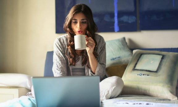 woman-in-grey-jacket sits on bed uses grey laptop